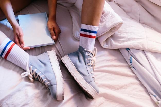 Vrouw in bed met blauwe pantoffels die thuis een boek beginnen te lezen