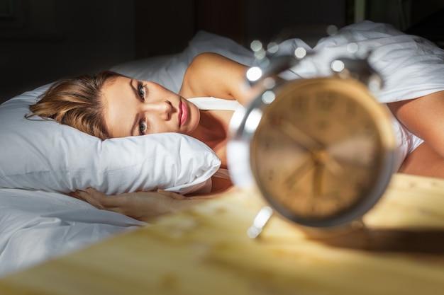 Vrouw in bed met slapeloosheid en nachtmerries kan niet slapen wachten tot haar wekker afgaat