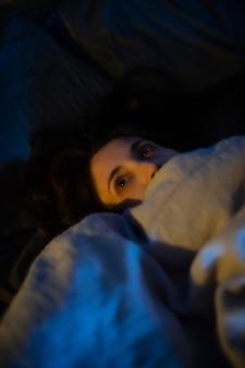 Vrouw in bed thuis met mysterieuze lichten om haar heen