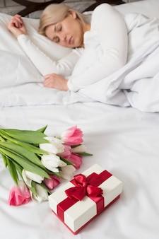 Vrouw in bed verrast met bloemen en cadeau