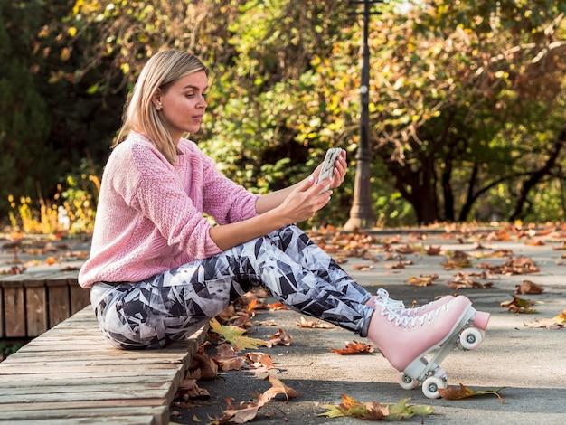 Vrouw in beenkappen en rolschaatsen die selfie nemen