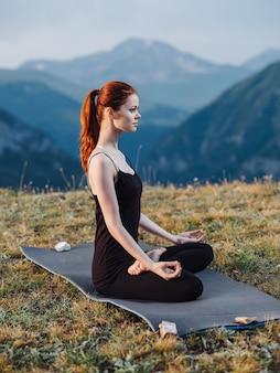 Vrouw in beenkappen mediteren zittend op een tapijt op de natuur in de bergen