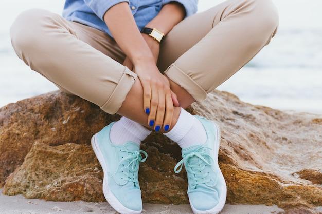 Vrouw in beige broek en een denim shirt en turquoise sneakers zittend op een rots bij de zee