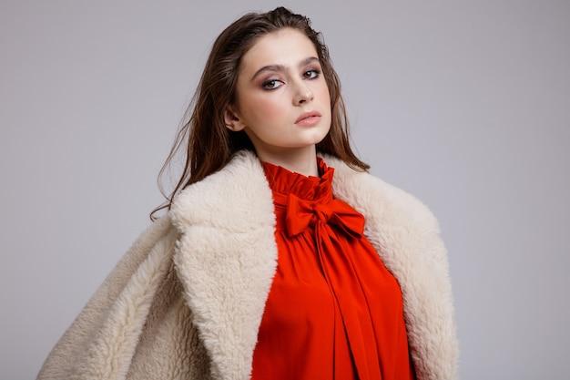 Vrouw in beige jas lange rok rode strik blouse laarzen op witte achtergrond bruin haar studio shot