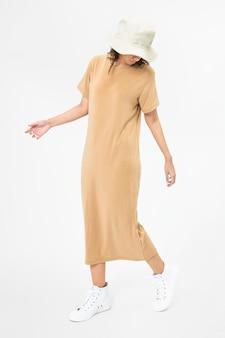 Vrouw in beige t-shirtjurk en emmerhoed vrijetijdskleding hat