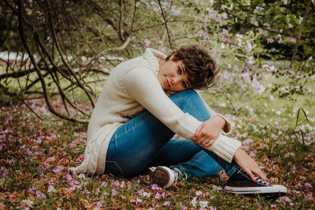 Vrouw in beige trui en blauwe spijkerbroek zittend in het bos