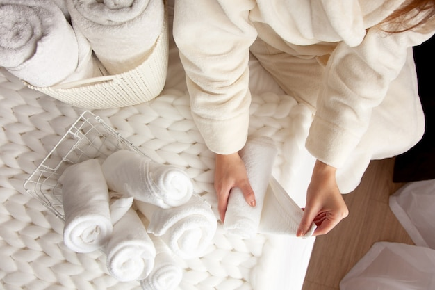 Vrouw in beige warm gewaad vouwt de schone witte handdoeken en zet in een metalen gaasmand op zwarte achtergrond. kopieer ruimte op zwarte achtergrond. netheid en organisatieconcept.