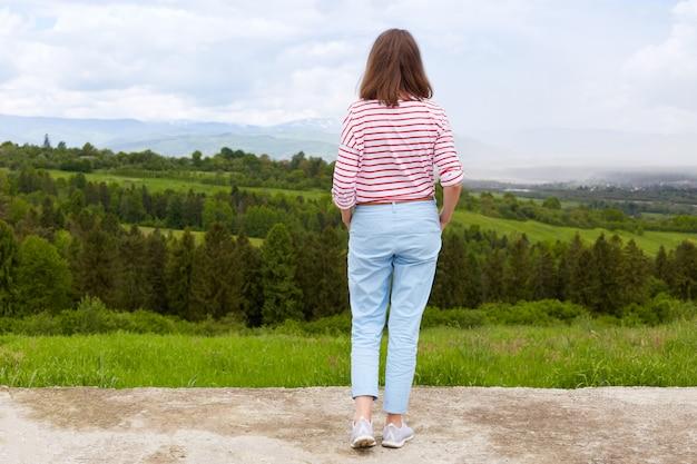 Vrouw in berg, panoramisch uitzicht op bergketen, bomen. groen gras. blauwe lucht, vrouw draagt casual broek en wit t-shirt