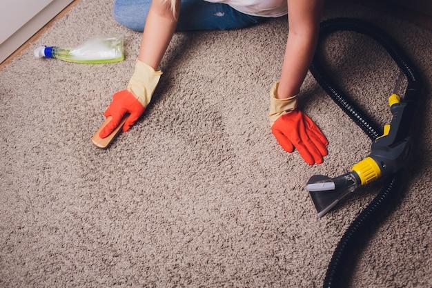 Vrouw in beschermend handschoen schoonmakend tapijt met borstel.