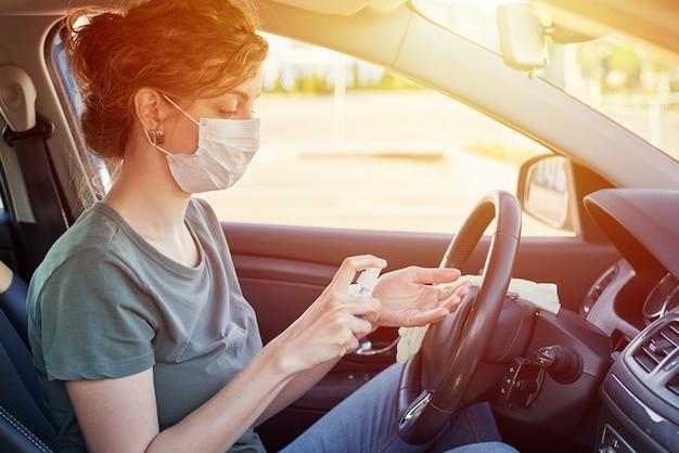 Vrouw in beschermend masker desinfecteren handen met antibacteriële spray in auto