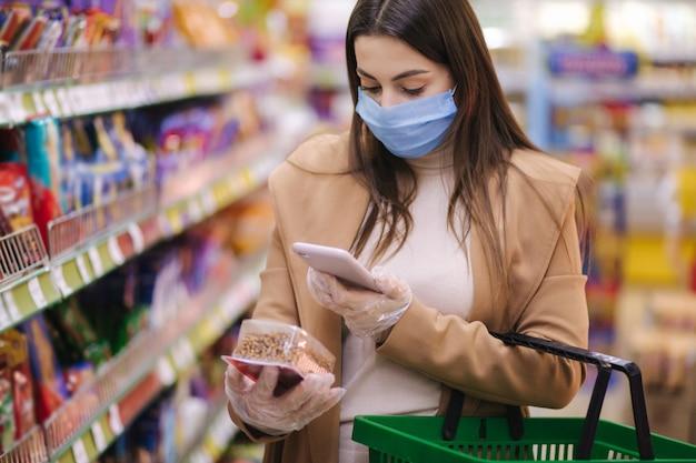 Vrouw in beschermend masker en handschoenen scannen label met prijs met behulp van telefoon bij goederen terwijl ze binnen staat