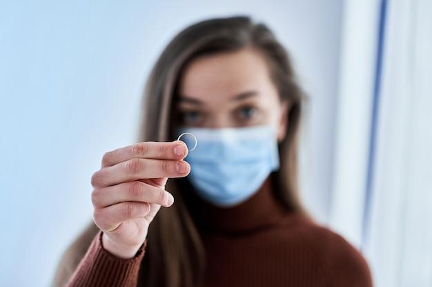 Vrouw in beschermend masker houdt ring. verbreek het huwelijk na samenwonen en thuis blijven met man in quarantaine en isolatie als gevolg van coronavirusepidemie. echtscheiding concept