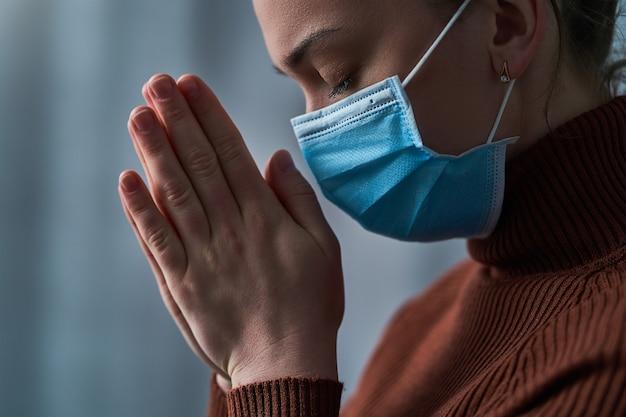 Vrouw in beschermend masker met gesloten ogen en biddende handen, vraagt god om genezing en herstel tijdens ziekte