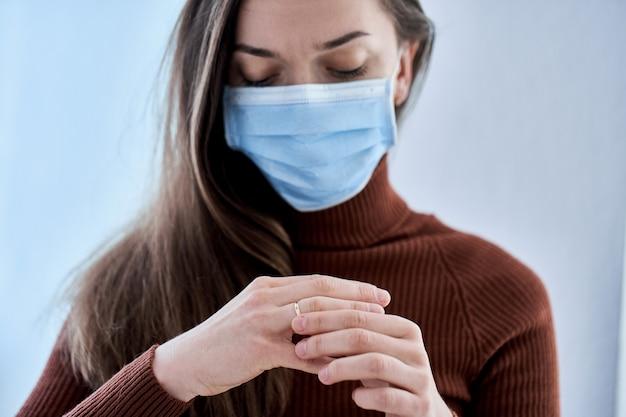 Vrouw in beschermend masker ring uit vinger verwijderen. verbreek de relatie en de scheiding na samenwonen tijdens quarantaine en isolatie als gevolg van coronavirus covidepidemie. echtscheiding concept