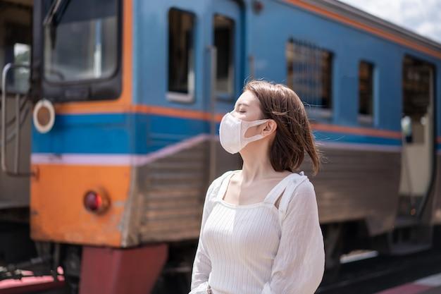 Vrouw in beschermend masker wachten op de lokale trein op het perron op het station.