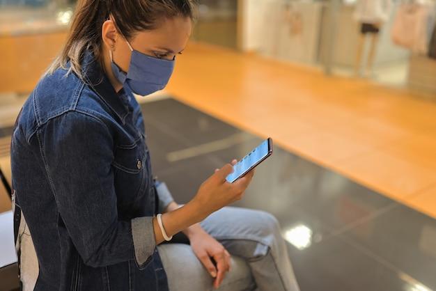 Vrouw in beschermend masker zitten op bankje in winkelcentrum en kijken naar telefoon