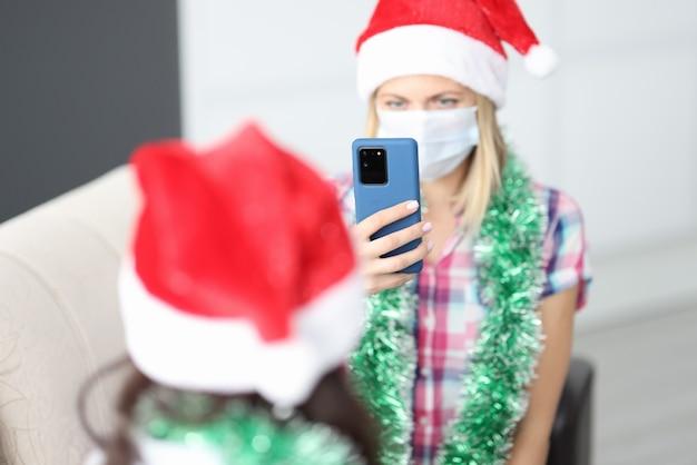 Vrouw in beschermend medisch masker en kerstman hoed zit op de bank en neemt foto's van haar vriendin op smartphone