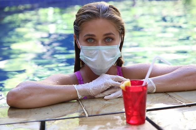 Vrouw in beschermend medisch masker geniet van zwemmen in het zwembad. coronavirus (covid-19.