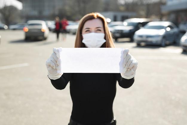 Vrouw in beschermend medisch masker houdt een leeg bordje vast zonder een inscriptie