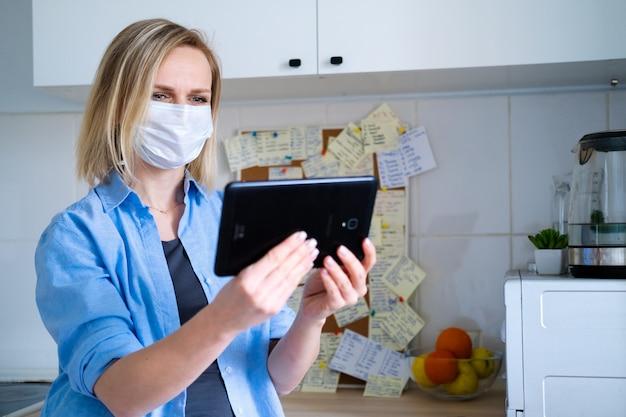 Vrouw in beschermend medisch masker met behulp van digitale tablet voor video-oproep praten vrienden en ouders, meisje om thuis te zitten keuken plezier begroeting online door computer webcam maken videocall