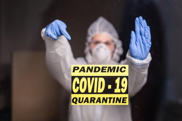 Vrouw in beschermend pak en in beschermend medisch masker dat eindegebaar toont. epidemioloog toont stop palm
