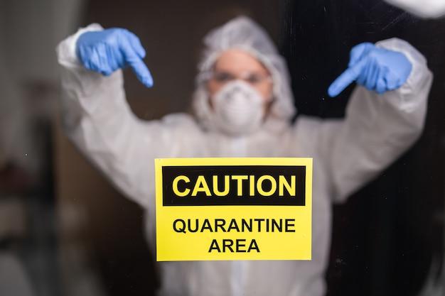 Vrouw in beschermend pak en in beschermend medisch masker dat teken toont. epidemioloog toont stop palm. stop het coronavirus of covid-19 en de pandemie