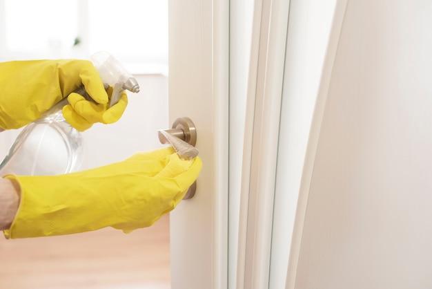 Vrouw in beschermende handschoenen die deurhandvat desinfecteren terwijl thuis het schoonmaken