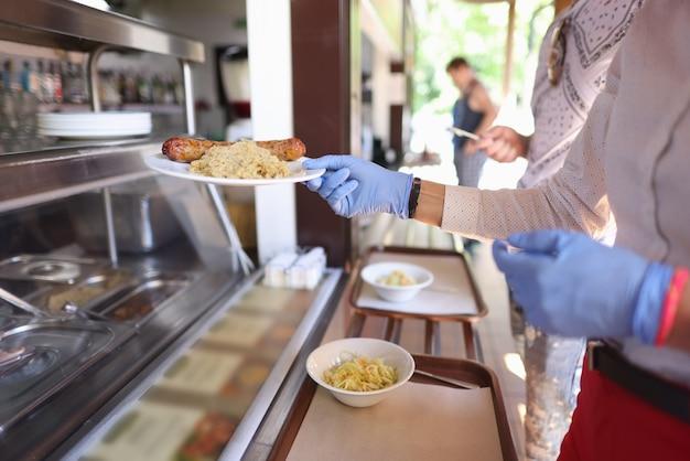 Vrouw in beschermende handschoenen in café neemt bord eten