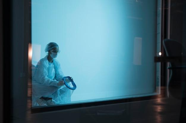 Vrouw in beschermende kleding in het ziekenhuis met kopie ruimte