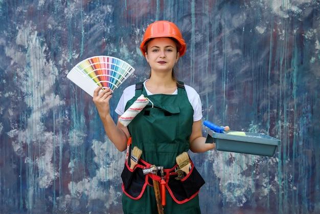 Vrouw in beschermende overall met dienblad en rolschilderijmuur