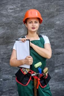 Vrouw in beschermende uniform en helm poseren met klembord en gereedschapsriem
