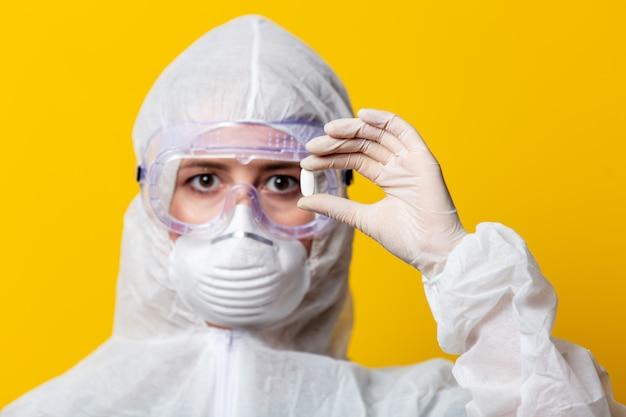 Vrouw in beschermingspak en masker houdt pil