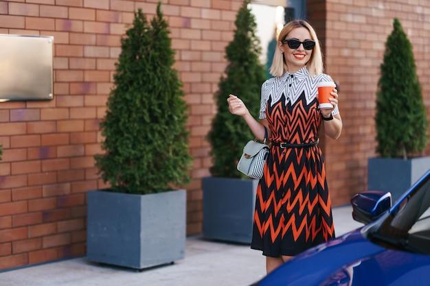 Vrouw in beweging met een kopje koffie tijdens het wandelen in de buurt van een auto in de stad