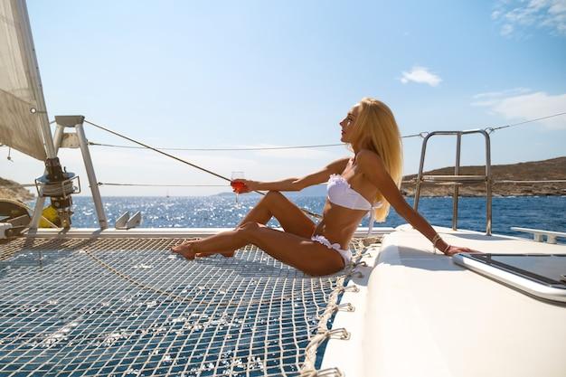 Vrouw in bikini bruint en drinkt wijn op een zomerse catamaranzeilcruise