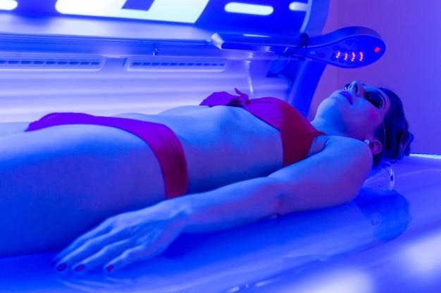 Vrouw in bikini die in wellnesskuuroordsolarium looit