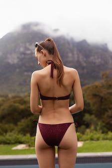 Vrouw in bikini die zich dichtbij poolside in de binnenplaats bevindt