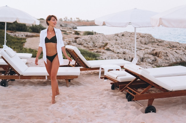Vrouw in bikini en wit overhemd door de oceaan