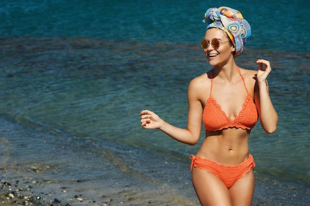Vrouw in bikini en zonnebril het strand