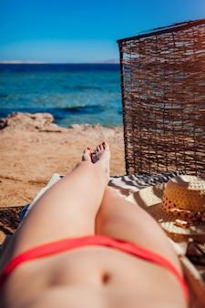 Vrouw in bikini het ontspannen op strand dat op chaise-longue met overzeese en bergmening ligt. zomervakantie.