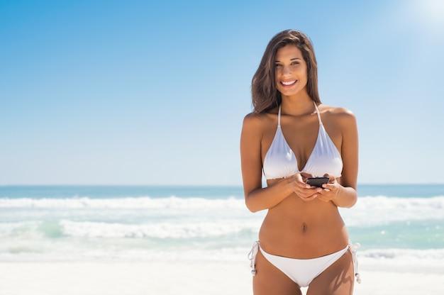 Vrouw in bikini met behulp van de telefoon