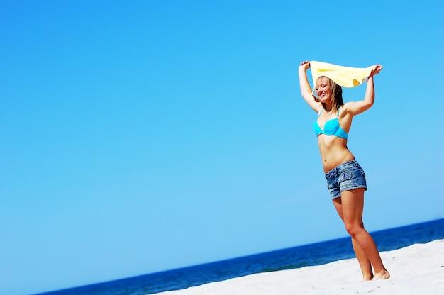 Vrouw in bikini met plezier op het strand
