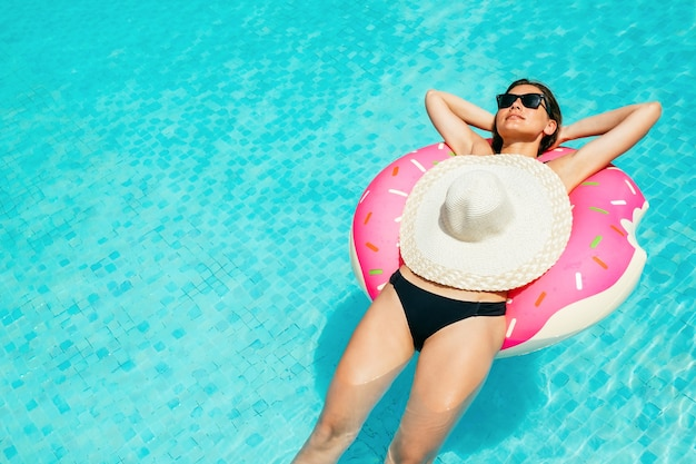 Vrouw in bikini op de opblaasbare matras in het zwembad