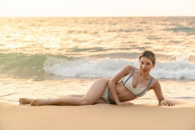 Vrouw in bikini op zand liggen, ontspannen zonnebaden.