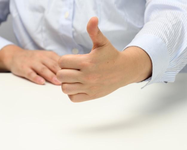 Vrouw in blauw gestreept shirt met als gebaar met linkerhand, goedkeuring en aanbeveling