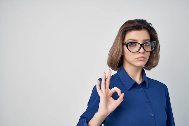 Vrouw in blauw shirt met bril manager kantoor lichte achtergrond