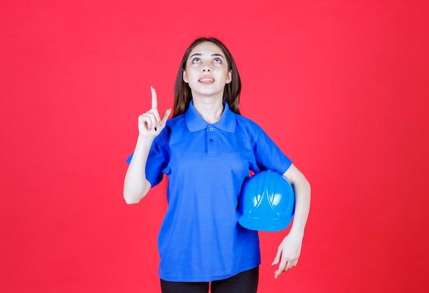 Vrouw in blauw shirt met een blauwe helm en ergens in de buurt wijzend.