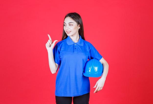 Vrouw in blauw shirt met een blauwe helm en ergens naar wijzend.