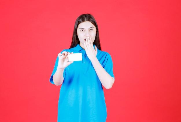 Vrouw in blauw shirt presenteert haar visitekaartje en wordt verrast en doodsbang.