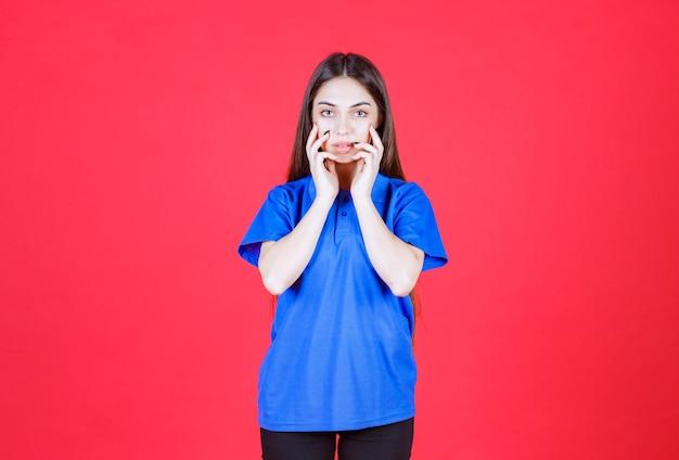 Vrouw in blauw shirt staande op rode muur en ziet er opgewonden en doodsbang uit.