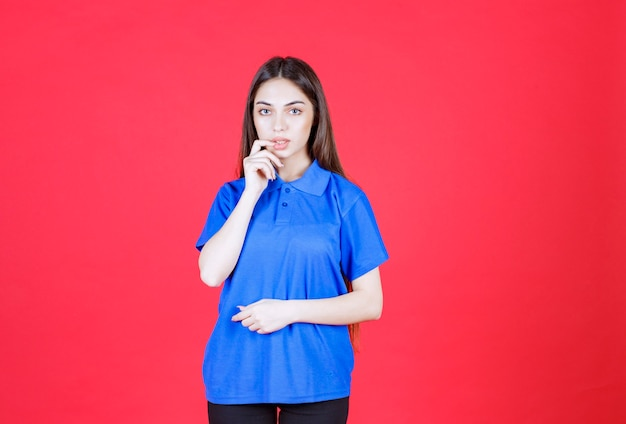 Vrouw in blauw shirt staande op rode muur en ziet er verward en attent uit.